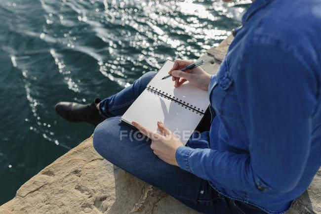 Giovane donna seduta sul molo scrivere in notebook — Foto stock