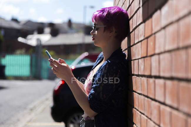 Young woman with dyed hair leaning against brick wall text messaging — Stock Photo