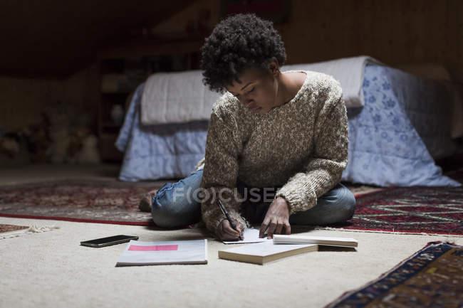 Giovane donna a casa seduta sulla scrittura di piano — Foto stock