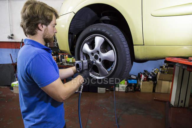 Mechaniker repariert Autorad in Werkstatt — Stockfoto
