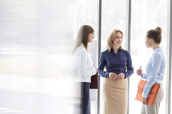 Три девушки, говорить в окне — стоковое фото