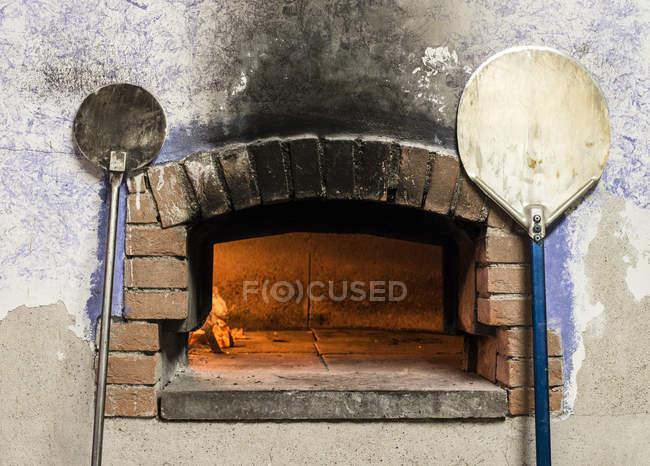 Aufgehellter Pizzaofen und Schalen in der Nähe platziert — Stockfoto