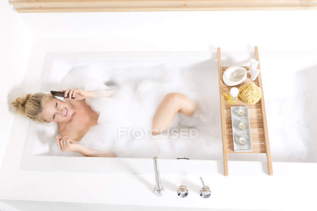 Woman on the phone in bubble bath — Stock Photo