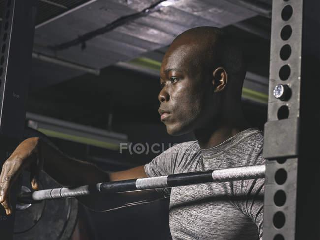 Physische Athlet ruht auf Langhantel im Fitness-Studio — Stockfoto