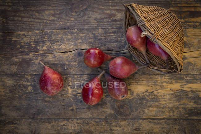 Wickerbasket e orgânico vermelho Clapp favorito na madeira escura — Fotografia de Stock