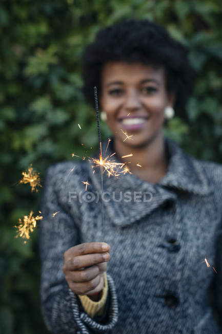Beautiful black woman lighting sparkler outdoor — Stock Photo