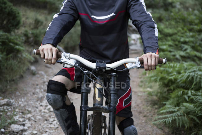 Cropped image of Mountainbiker on forest path — Stock Photo