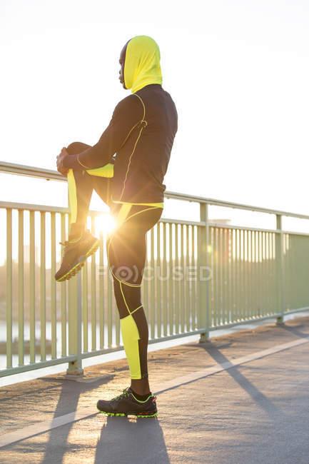 Спортсмен растягивается на перилах моста в городе — стоковое фото