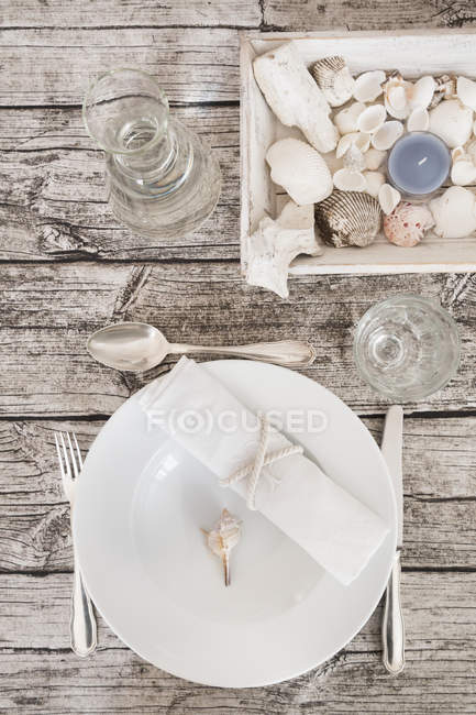 Place setting with water carafe on maritime laid table — Stock Photo
