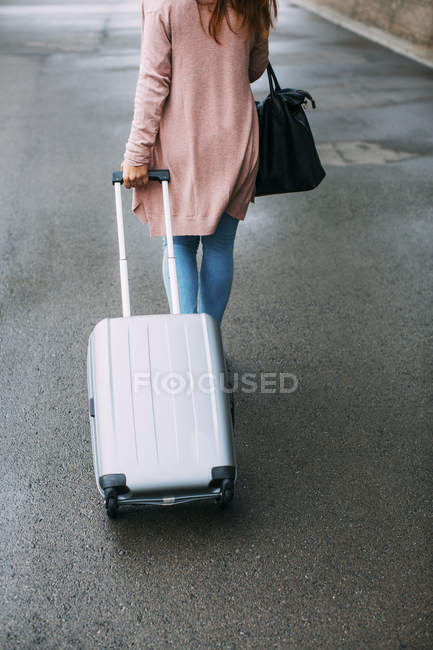 Walking woman with wheeled luggage on street — Stock Photo