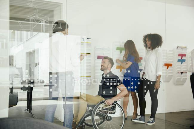 Колеги говорять в офісі з одного сидячи в інвалідному візку — стокове фото