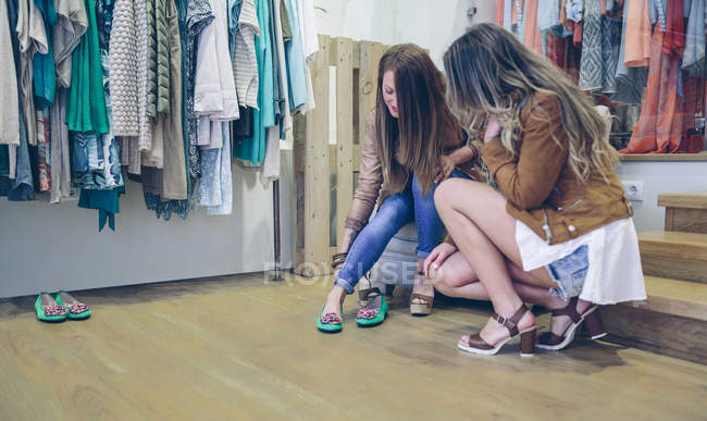 Two women shopping for shoes in a boutique — Stock Photo
