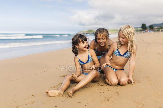 Spain, Colunga, three girls sitting on the beach having fun — Stock Photo