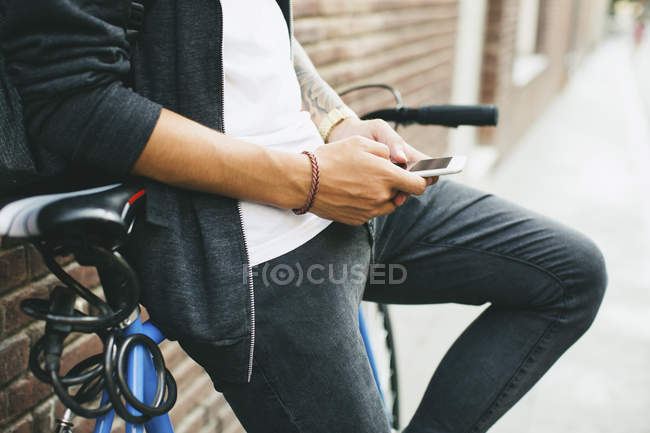 Teenager with a fixie bike texting on smartphone leaning on wall — Stock Photo