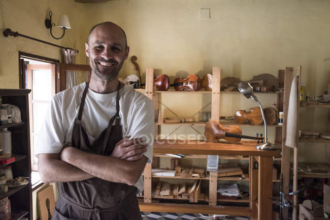 Portrait of smiling luthier in his workshop — Stock Photo