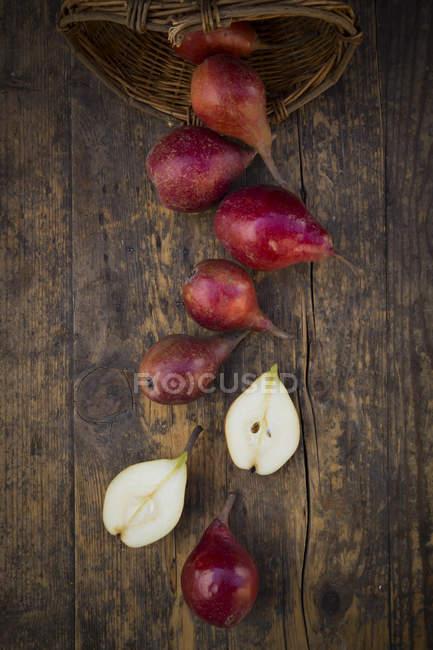 Inteiro e fatiado orgânico vermelho Clapp favorito na madeira escura — Fotografia de Stock