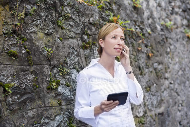 Blond woman standing in front of rock face telephoning with smartphone — Stock Photo