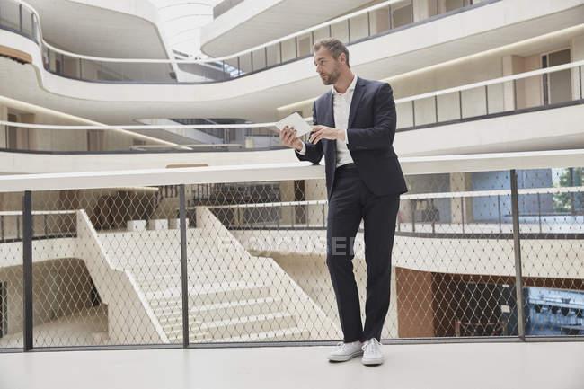 Homme d'affaires utilisant une tablette dans un immeuble de bureaux — Photo de stock