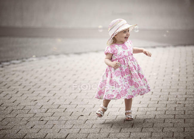 Happy blond little girl wearing hat and summer dress with floral design  dancing on pavement — Stock Photo