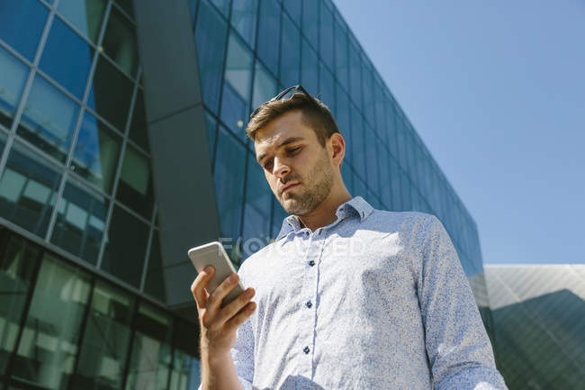 Businessman looking at cell phone — Stock Photo