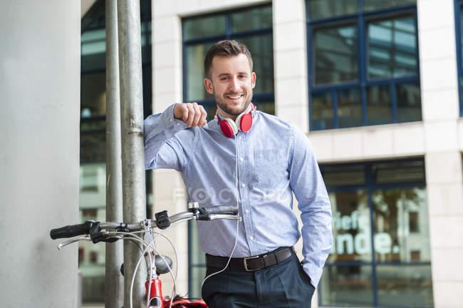 Portrait de jeune homme souriant portant des écouteurs à l'extérieur — Photo de stock