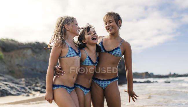 Іспанія, напрямку Colunga, три дівчини стоять рука об руку на пляжі весело — стокове фото