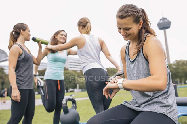 Женщина, проверка наручные часы с женщинами, расслабиться после тренировки на фоне — стоковое фото