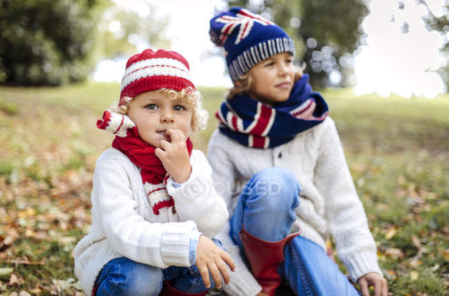 Portrait of blond little boy and his brother in the background  wearing fashionable knit wear in autumn — Stock Photo