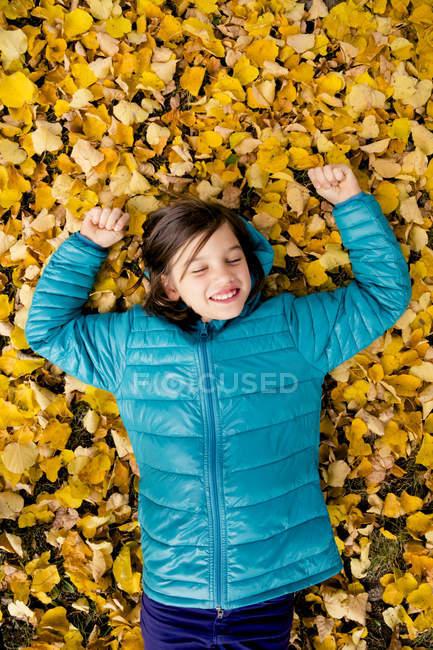 Sonriente chica acostada en el suelo cubierta de hojas de otoño - foto de stock