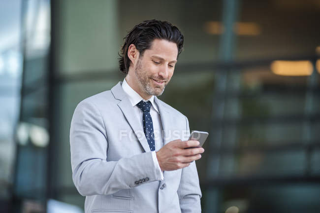 Smiling businessman looking at smartphone — Stock Photo