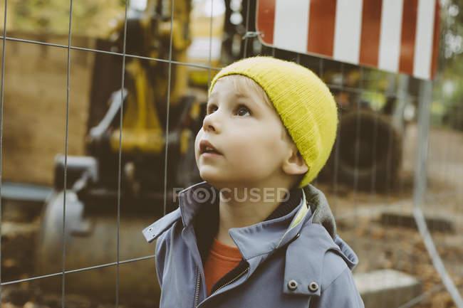 Retrato de menino com chapéu de lã amarelo em pé em frente ao canteiro de obras — Fotografia de Stock