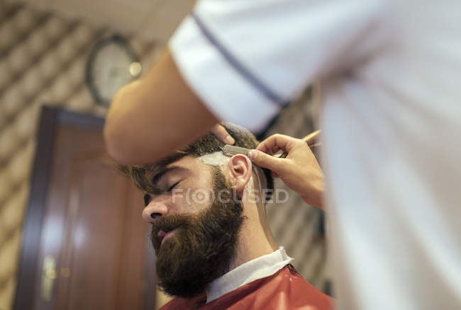 Barber shaving beard of a customer in barbershop — Stock Photo