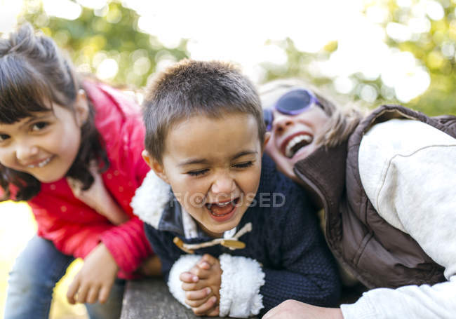 Little children lying on front on boardwalk and laughing in park — Stock Photo