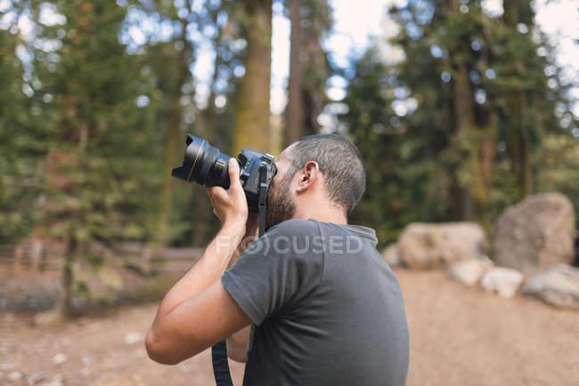 Uomo giovane turista fotografare nella foresta — Foto stock