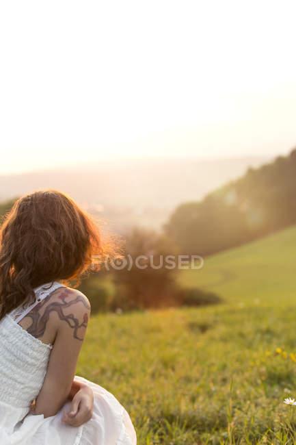 Rückansicht einer Frau auf der Alm beim Sonnenaufgang — Stockfoto