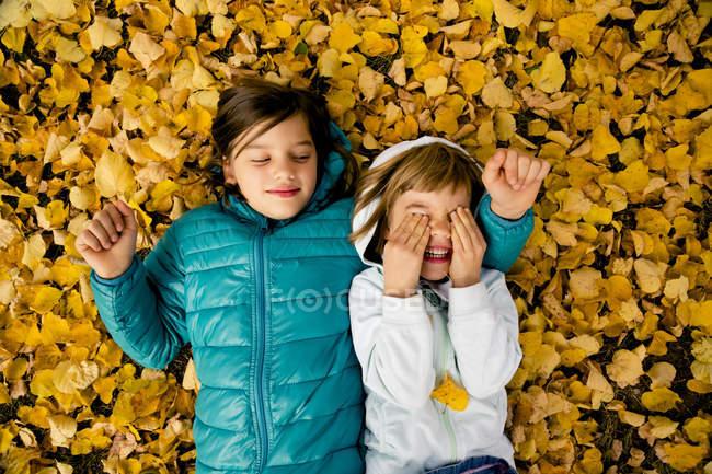 Duas meninas deitadas lado a lado no chão cobertas com folhas de outono — Fotografia de Stock