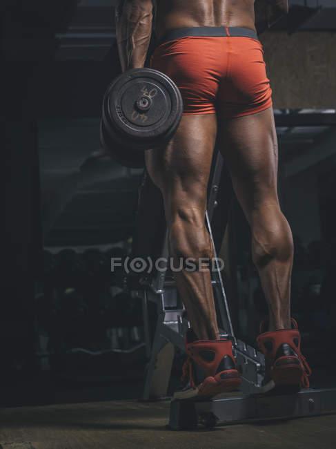 Bodybuilder Training Kälber in dunklen Turnhalle — Stockfoto