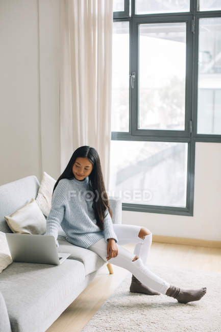 Smiling young woman sitting on couch at home using laptop — Stock Photo