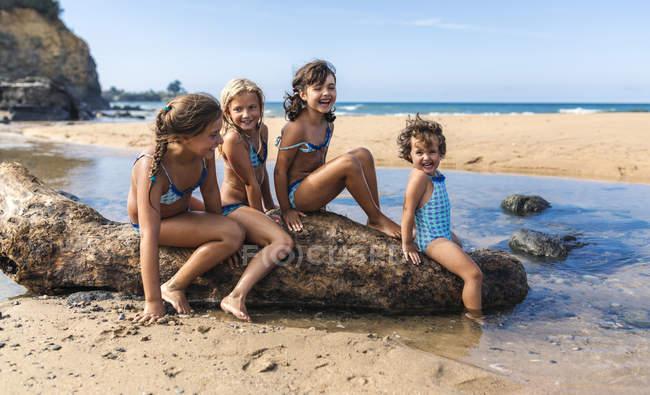 Spain, Colunga, four girls sitting on dead wood on the beach — Stock Photo