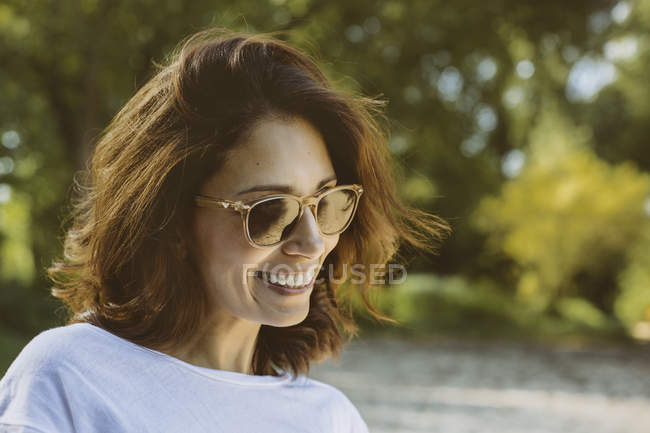 Portrait of smiling woman with brown hair wearing sunglasses — Stock Photo