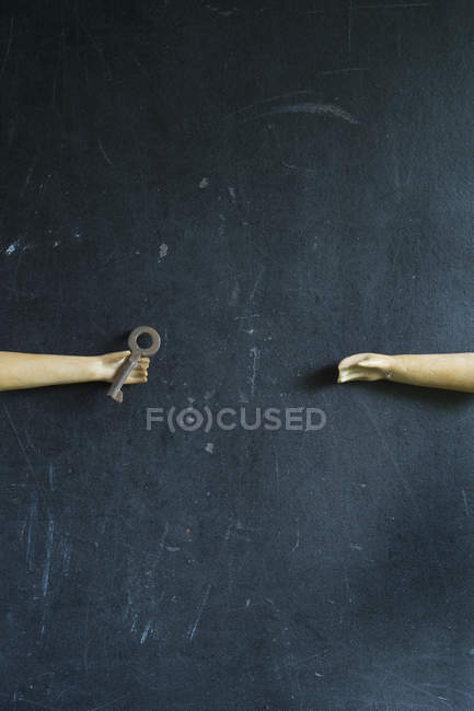 Closeup view of two toy hands with key on black surface — Stock Photo