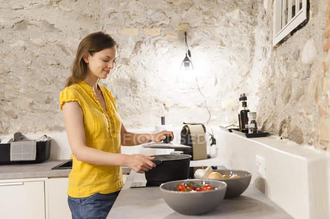 Frau in der Küche hält Topf GAP, Seitenansicht — Stockfoto