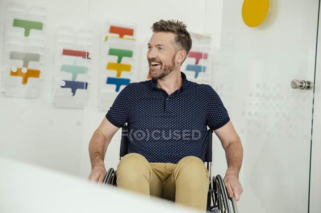 Улыбающийся человек в инвалидной коляске в современном офисе — стоковое фото