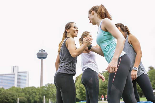 Четыре счастливые женщины пожимают руки после тренировки на открытом воздухе — стоковое фото