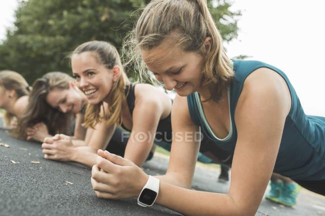 Cuatro mujeres haciendo planchas durante el entrenamiento al aire libre en el Parque - foto de stock