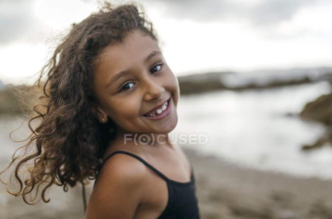 Smiling little mixed race girl on beach in Gijon, Spain — Stock Photo