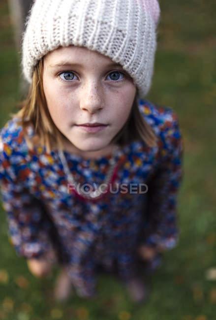 Retrato de menina séria usando tampa de lã olhando para a câmera — Fotografia de Stock