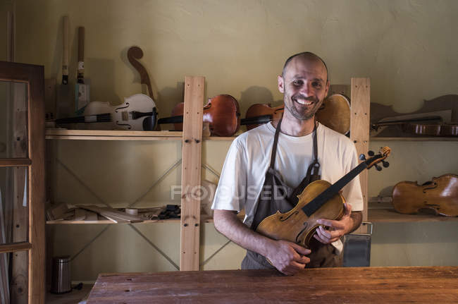 Smiling luthier holding a violin in his workshop — Stock Photo