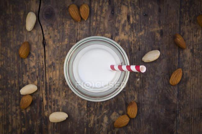 Миндальное молоко в стекле, соломинка, на деревянной поверхности — стоковое фото