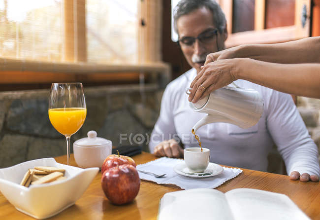 Man sitting at breakfast while woman hands pouring coffee into his cup — Stock Photo